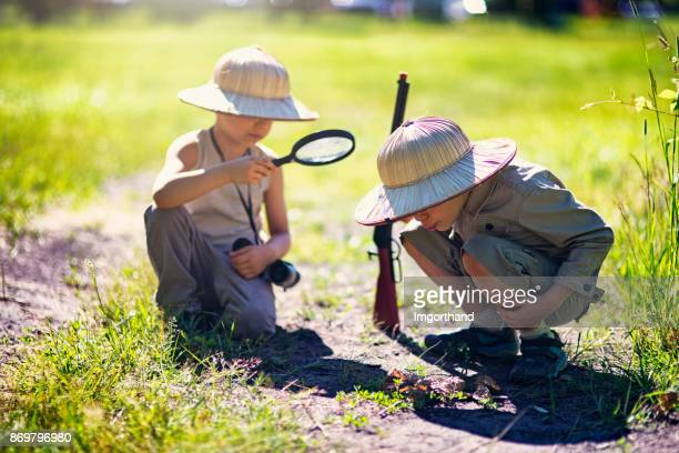 Little safari boys starting fire with magnification glass