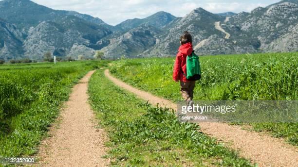 little school boy walking on dirt country road - schulkind nur jungen stock-fotos und bilder