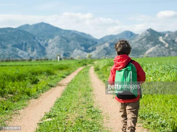 Pequeña escuela niño caminando en tierra camino del país