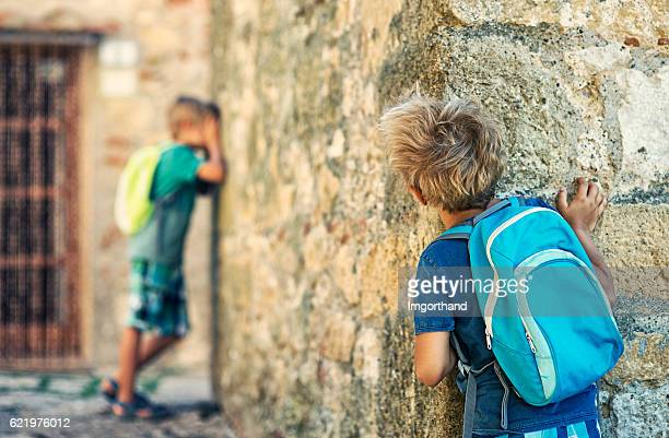little school boys playing hide and seek - children only stock pictures, royalty-free photos & images