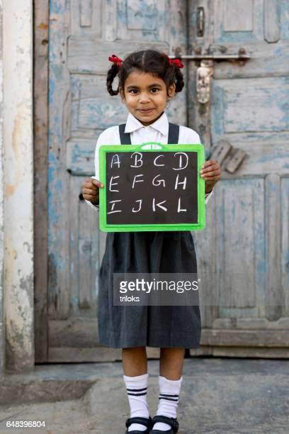 Little school girl holding slate