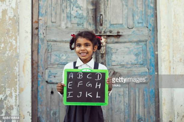 little school girl holding slate - village stock pictures, royalty-free photos & images