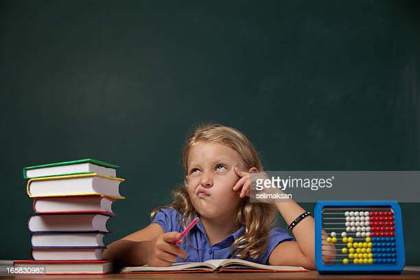 Little school girl thinking on desk before blackboard