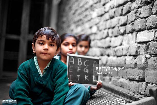 Little School Students portrait at home holding chalkboard