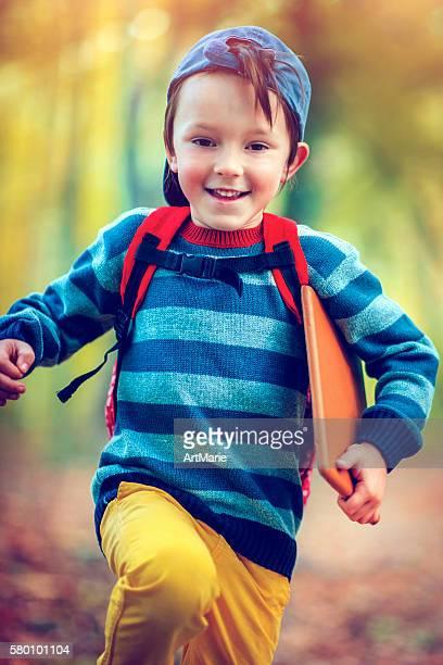 Little schoolboy in autumn