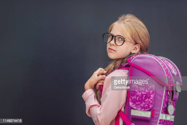 little schoolgirl with backpack black background