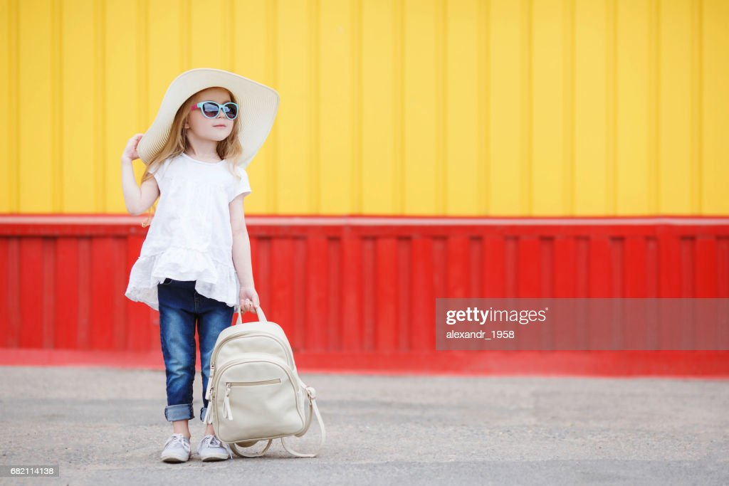 Little schoolgirl with a white backpack : Stock Photo
