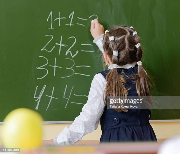 little schoolgirl writing on blackboard - little russian girls stock photos and pictures