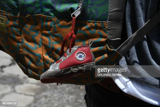 A little shoe that belongs to his baby girl hangs from the backpack of Honduran immigrant Ever Sierra who was deported from the US and arrived in San...