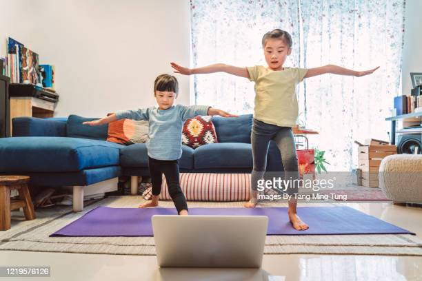 little sibling enjoy online yoga class with laptop computer at home. -  eラーニング ストックフォトと画像