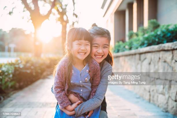 little sibling hugging & playing joyfully on the street during sunset - children only stock pictures, royalty-free photos & images