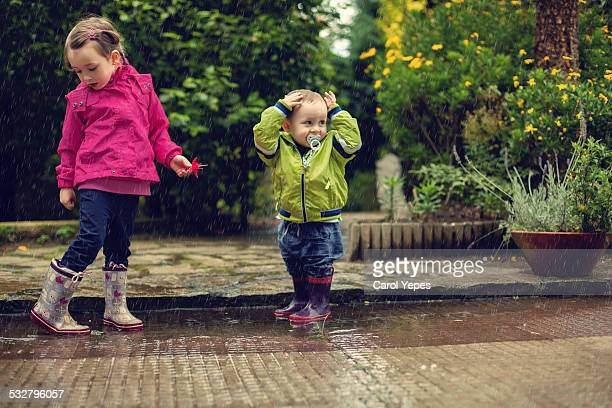 Little sibling playing in puddles