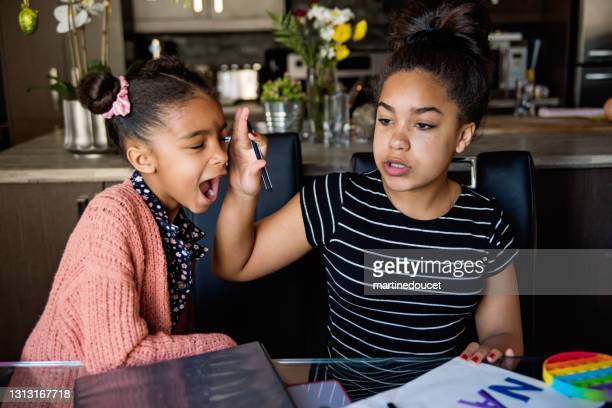 """little sister nagging big sister homeschooling on the dining room table. - """"martine doucet"""" or martinedoucet stock pictures, royalty-free photos & images"""