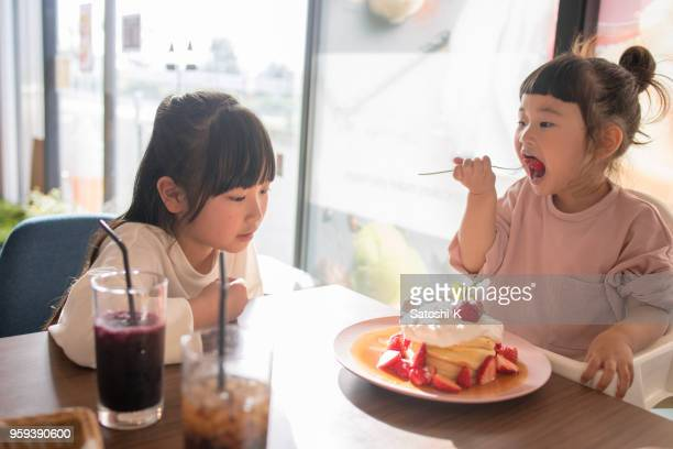 little sisters eating hot cakes in cafe - japanese girls hot stock photos and pictures