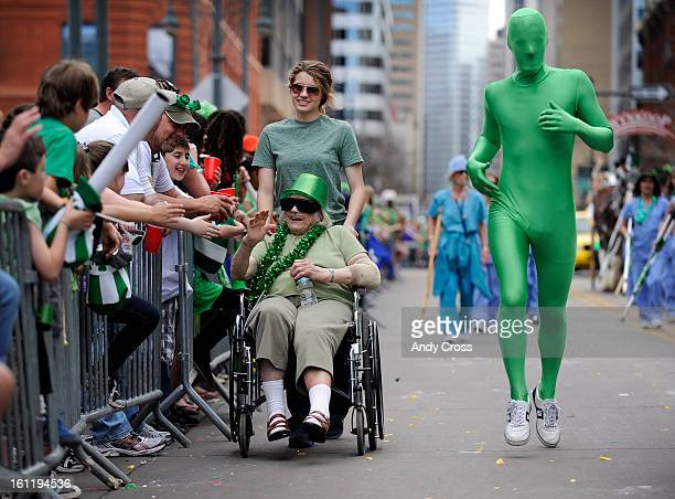 Little Sisters of the Poor entrant and resident Pauline Snyder 80yearsold gets highfives from fans as helper Taylor Nelson wheels her down the parade...