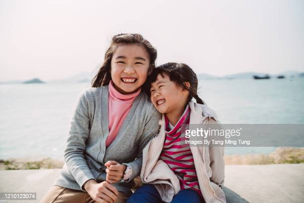little sisters talking joyfully in promenade - side by side stock pictures, royalty-free photos & images