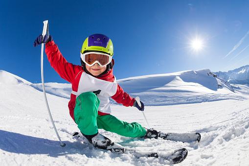 Little skier having fun at sunny snowy day 651792260