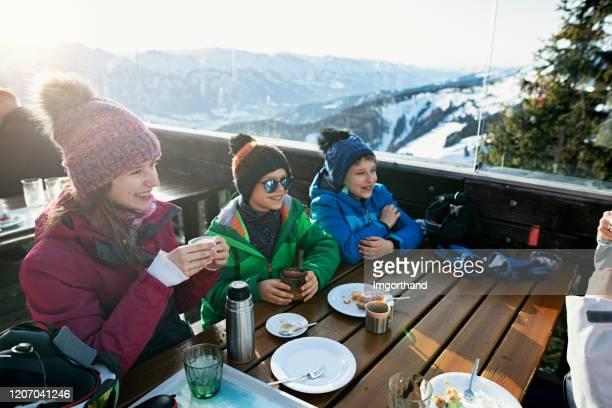 petits skieurs mangeant le déjeuner dans le bar de ski alpin - sport d'hiver photos et images de collection
