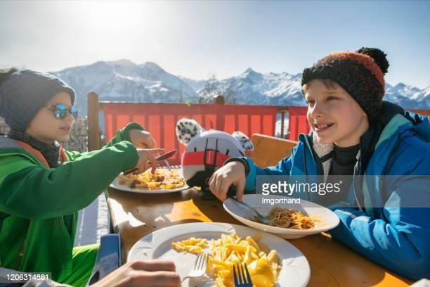 petits skieurs déjeunant dans le restaurant de ski alpin - sport d'hiver photos et images de collection