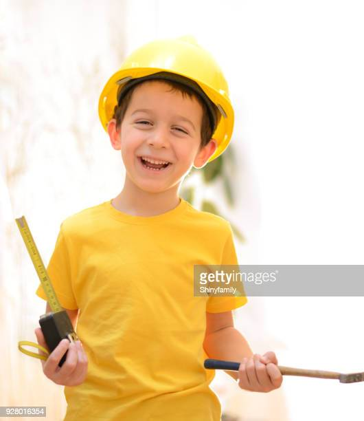 Weinig lachende bouwer met hamer en meetlint