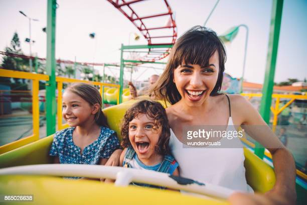 little son and daughter with mother on roller coaster ride - carnival stock photos and pictures