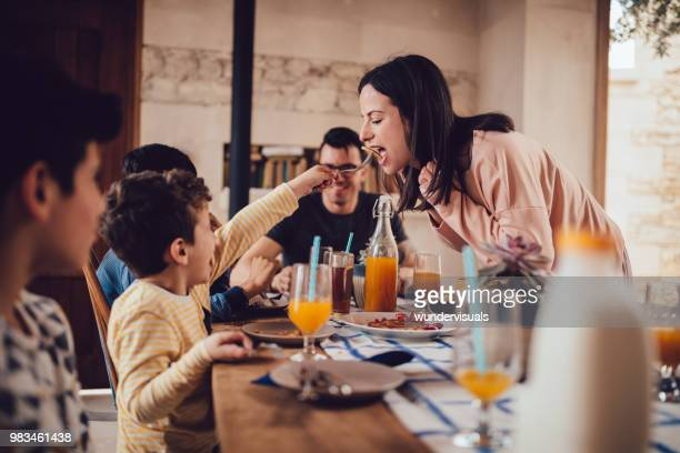 little son giving mother pancake during breakfast with family - brunch stock pictures, royalty-free photos & images