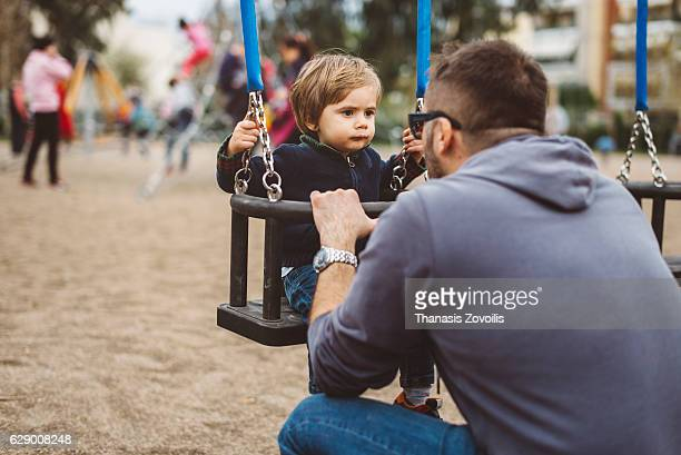 Little son swinging in park with his father