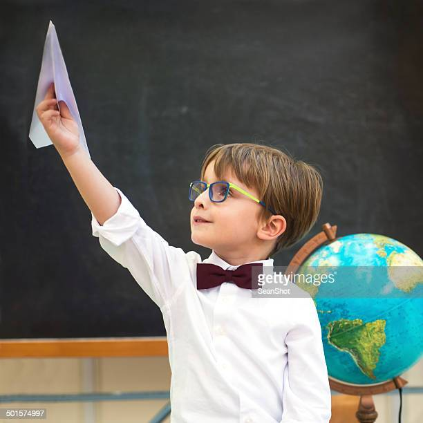 Little Student Playing with a Paper Airplane in the Classroom