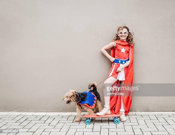 Poco Chica con su Perro superhéroe y monopatín
