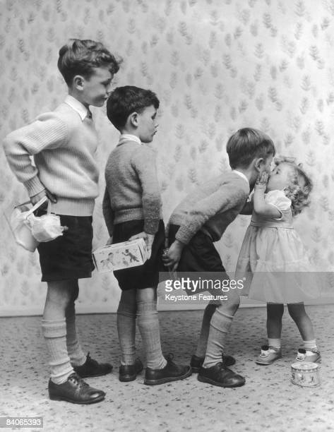 Little Susan Burton exchanges a kiss for a present from each of her brothers on her second birthday in Ilford 30th November 1956 From left to right...