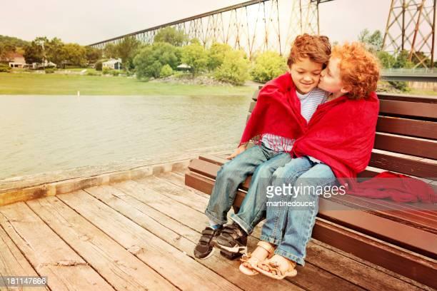 Little sweethearts Küssen und kuscheln Sie auf einer Bank.