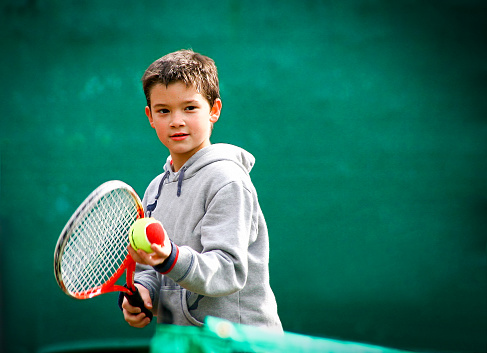 Little tennis player on a blurred green background 877754132