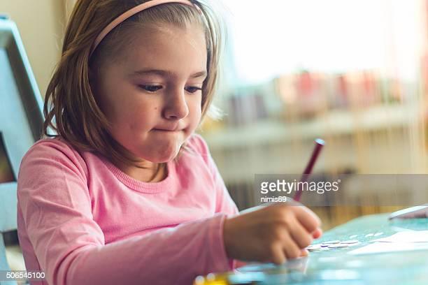 Wenig müde Mädchen Sitzen am Schreibtisch