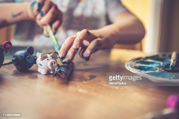 little toddler boy colorfully painting handmade clay pig - clay stock pictures, royalty-free photos & images