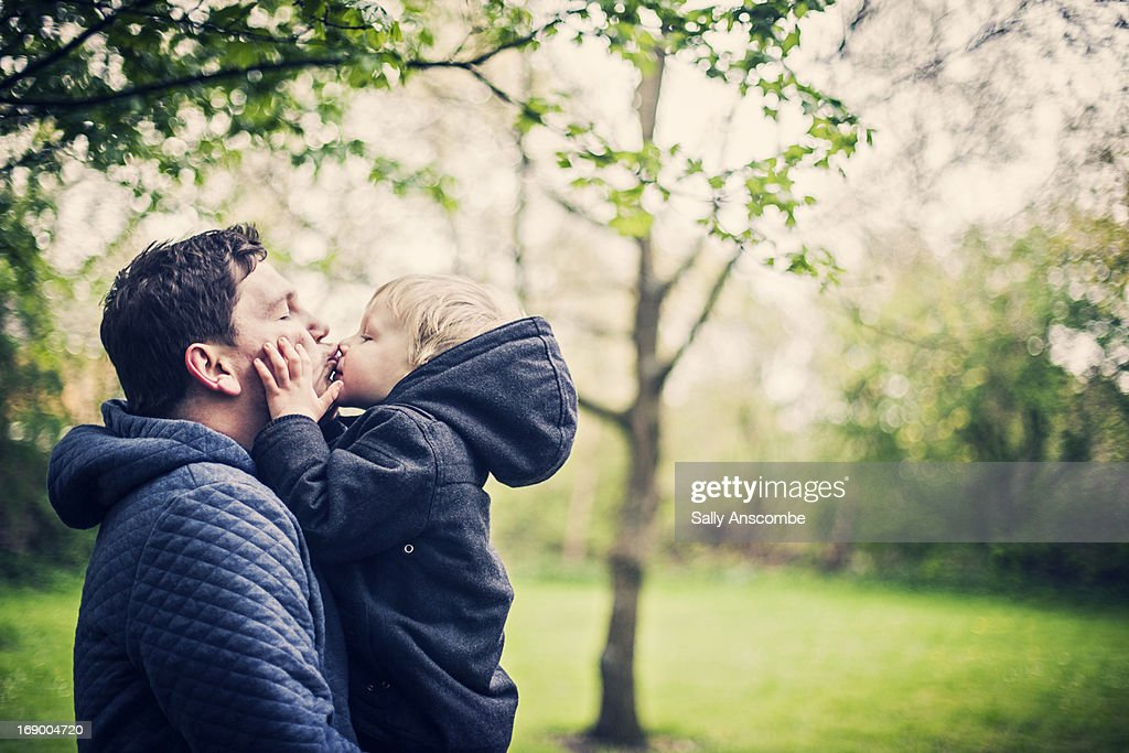 Little toddler boy giving his Daddy a kiss : Stock Photo