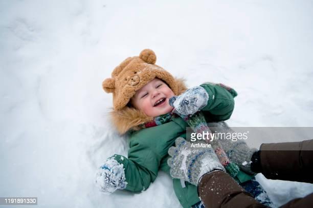 petit garçon d'enfant en bas âge ayant l'amusement dans la forêt d'hiver avec la neige à l'extérieur. concept d'hiver et de mode de vie - froid humour photos et images de collection