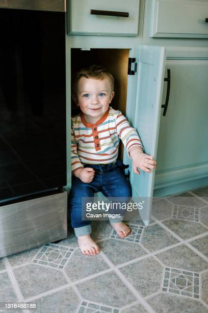 little toddler boy hiding in kitchen cabinet playing hike and seek - lino stock pictures, royalty-free photos & images