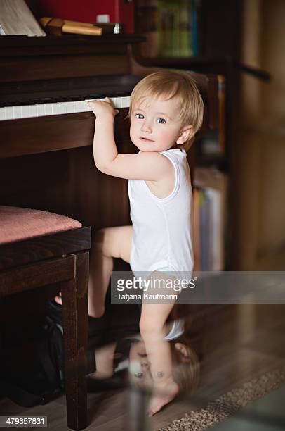 Little Toddler Boy trying to climb up a Piano