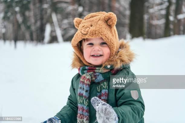 petit garçon d'enfant en bas âge marchant dans la forêt d'hiver et ayant l'amusement avec la neige appréciant l'hiver dehors. concept d'hiver et de mode de vie - froid humour photos et images de collection