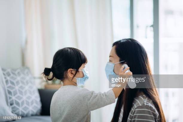 little toddler girl checking her sick mother's temperature with a digital thermometer in the living room, both of them are wearing a surgical mask to prevent the spread of cold and flu and viruses - digital thermometer ストックフォトと画像