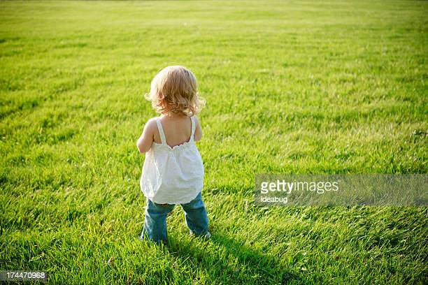 little toddler girl standing outside, with copy space - guess jeans stock photos and pictures