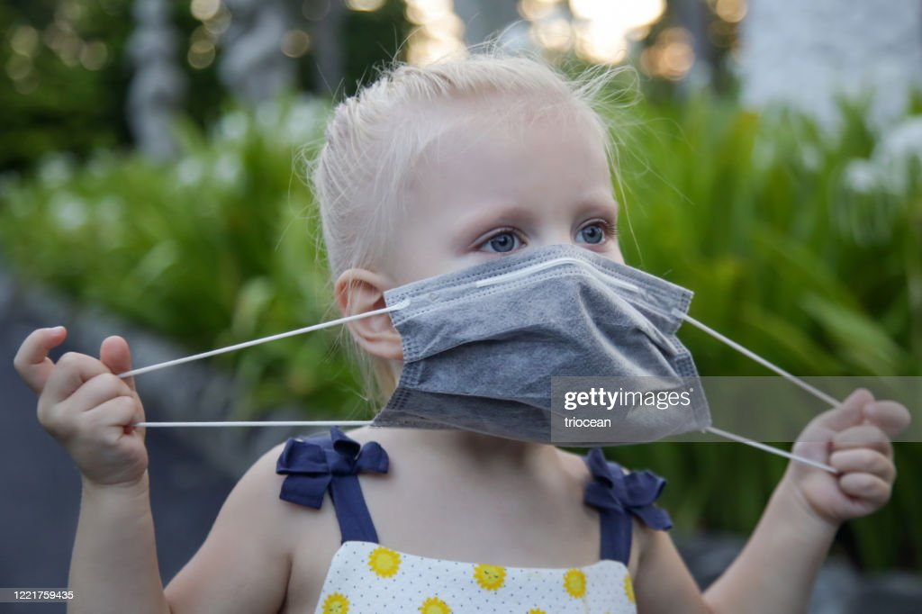 Little toddler girl trying to put medical protective mask. Candid outdoor portrait of child with medical mask. Corona virus outbreak or air pollution concept. : Stock Photo
