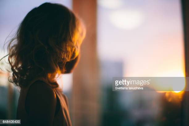 Little toddler girl watching on sunset