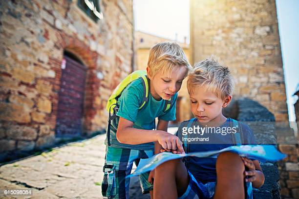 Little tourist boys checking map in a small Italian town