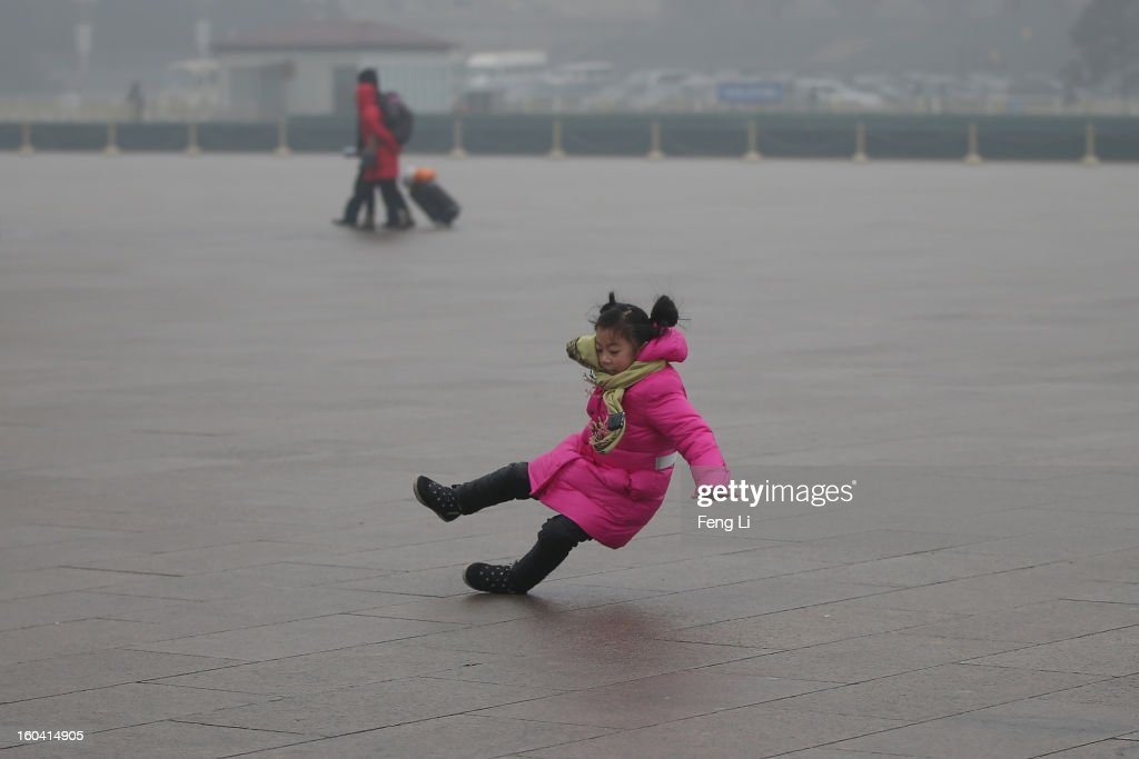 A little tourist falls on the ground with frozen ice at the Tiananmen Square during severe pollution on January 31, 2013 in Beijing, China. Heavy smog that has choked Beijing for the last five days weakened slightly on Thursday due to a light rainfall, although the capital's air remains heavily polluted. The haze choking many Chinese cities covers a total area of 1.43 million square kilometers, the China's Ministry of Environmental Protection said Wednesday.