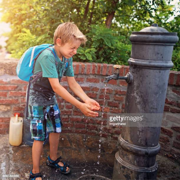 Little tourist splashing face with water from public fountain