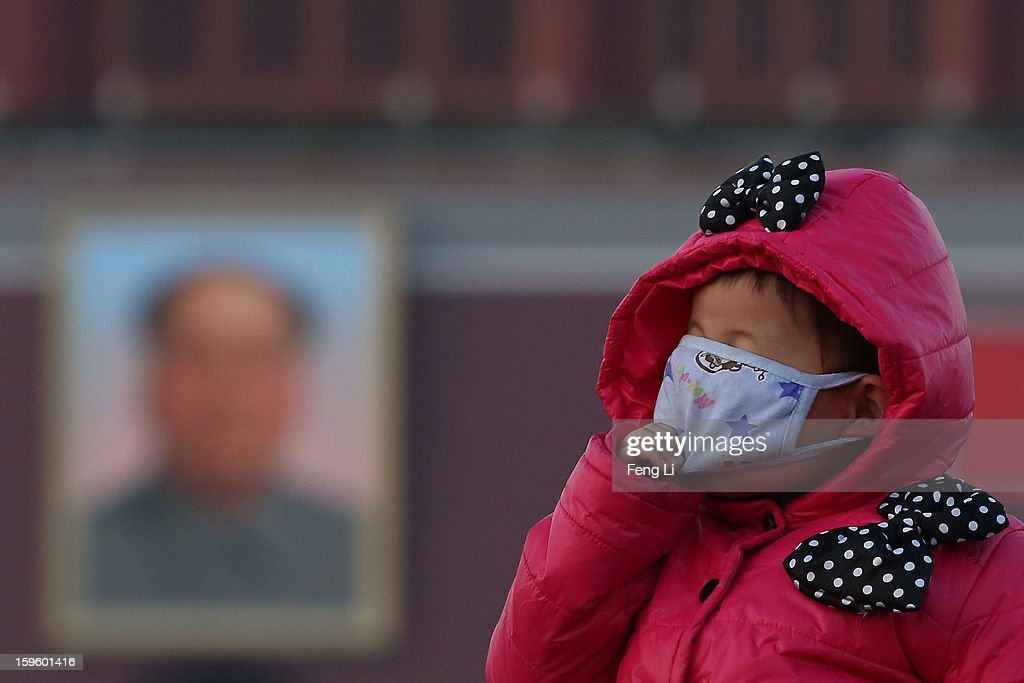 A little tourist wearing the mask at the Tiananmen Square during slight pollution on January 17, 2013 in Beijing, China.