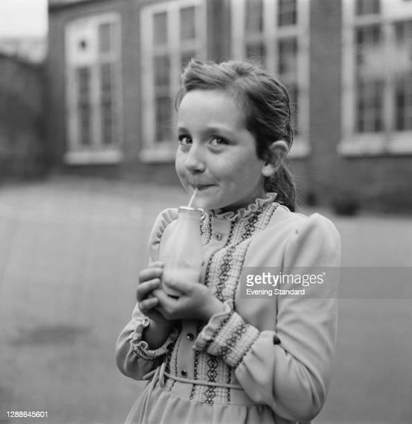 Little Tracy Cuthbert drinking a bottle of milk at Woodhill Primary School in Greenwich, London, UK, October 1971. Education Secretary Margaret...