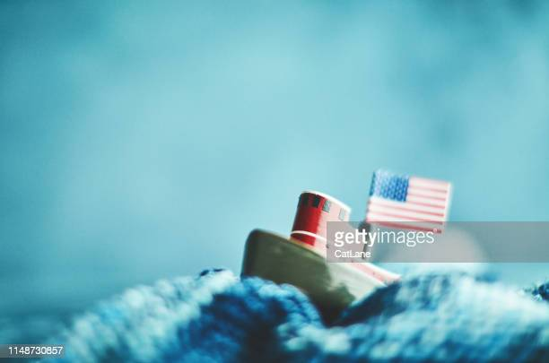 little tugboat with american flag in handmade waves - labor day stock pictures, royalty-free photos & images