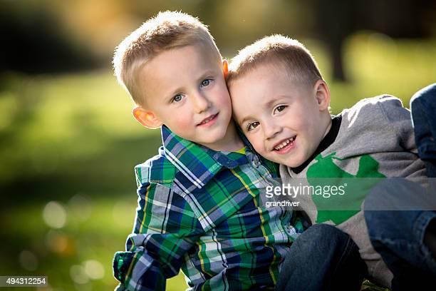 Kleine Zwei Brüder umarmen auf dem Rasen